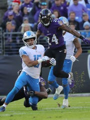 Lions wide receiver Golden Tate tackled by the Ravens'