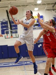 Going in for a layup is Salem's Maddie Kernahan (10), with Canton's Peyton Bagnell (12) at right.
