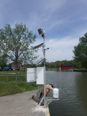 Michael Zieserl with JOA Surveys installs a microwave water level sensor on Saginaw Bay at Sebewaing, in May 2017. The sensor sends microwaves down to the water, and the water's height is calculated using the time it takes for the reflected waves to travel back from the surface. The sensor's height is linked to a fixed point on land marked by a brass disc, which allows us to account for any movement of the sensor or land. It collects data every six minutes and sends it to NOAA via satellite. The data collection point is one of many throughout the Great Lakes region helping U.S. and Canadian officials update the International Great Lakes Datum, a measurement of lake levels.