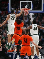 Miles Bridges dunks over Bucknell center Nana Foulland during the second half.