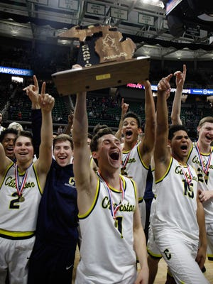 Foster Loyer (1) and his teammates celebrate Clarkston's 81-38 win in the Class A state title game Saturday at Breslin Center.