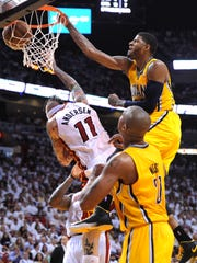 Pacers Paul George slams the ball home as the Heat's