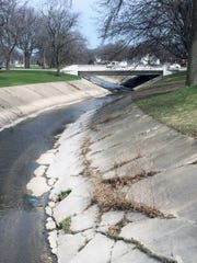 Cracked and broken concrete bed of the Kinnickinnic River at Pulaski Park will be removed in 2019 as part of an $8.6 million flood control project that will include widening the channel west of S. 16th St.