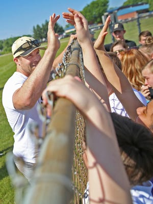 Noblesville West Middle School science teacher Jason Seaman is greeted by his students, over a fence, at the IHSAA baseball championships, the Noblesville vs Hamilton Southeastern game, Monday, May 28, 2018.  This is the first time his students have seen him since Friday May 25's school shooting.  When a student opened fire in the seventh grade science classroom, Seaman intervened to stop the shooter from shooting more students.  He and one student were shot in the incident.  He was shot three times.  He told the students he couldn't hug them just yet, because he was still a little tender, but he could high five them.