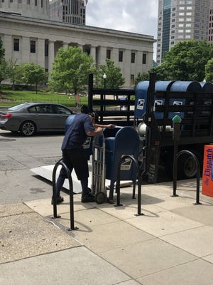 A Postal worker removes mailboxes in downtown Columbus, Ohio on May 29, 2020. He said they were being removed because of damage in the area after protests the night before. The boxes were returned Aug. 21.  BETHANY BRUNER