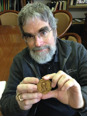 Vatican astronomer and Jesuit Brother Guy Consolmagno, who grew up in the Detroit-area, displays the Carl Sagan Medal he was awarded last week for his distinguished work in explaining the planetary sciences to the public. Consolmagno visited the Cranbrook Institute of Science Monday to retrieve meteorite samples from the Vatican's collection that he loaned the museum 12 years ago.