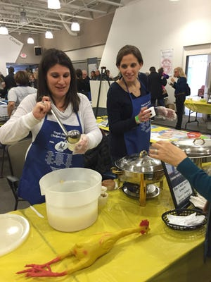 Elana Schwartz and Ariella Monson, 33, of Novi dish out Savta's Cincinnati Matzoh Ball Soup at the 5th Annual Chicken Soup contest Sunday, presented by Temple Shir Shalom.