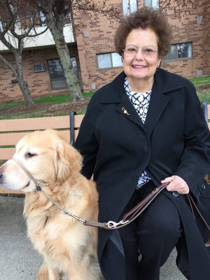Angie Done, 66, of Troy sits with her dog, Kramer, outside her apartment.