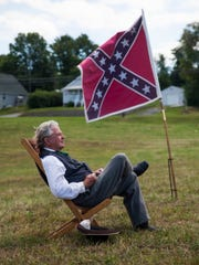 """David Meisky, a living historian playing Confederate Major General William """"Extra Billy"""" Smith, listens to a sermon during a Civil War reenactment to commemorate the 150th and 149th anniversaries of the first and second battles of Waynesboro at Coyner Springs Park on Sunday, Aug. 31, 2014."""
