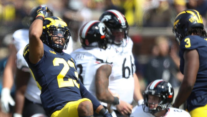 Michigan's Tyree Kinnel celebrates a sack on Cincinnati's Hayden Moore (8) in the second quarter Saturday, September 9, 2017 at Michigan Stadium.