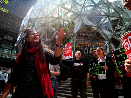Seattle City Councilwoman Kshama Sawant, left, speaks