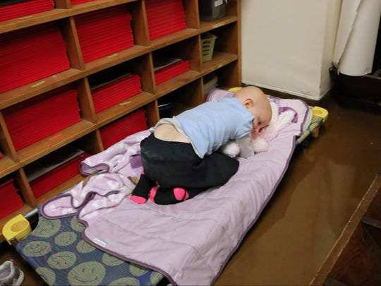 Amanda Conrow lays on her special cot on a room next to her kindergarten classroom at School 52.