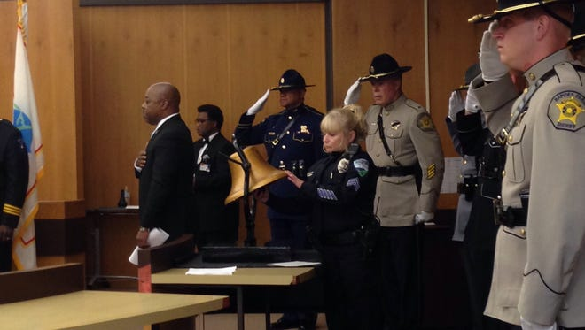 Law enforcement members stand at attention as Alexandria Police Sgt. Dawn Armer rings the bell 33 times in remembrance of Central Louisiana officers who have died in the line of duty.