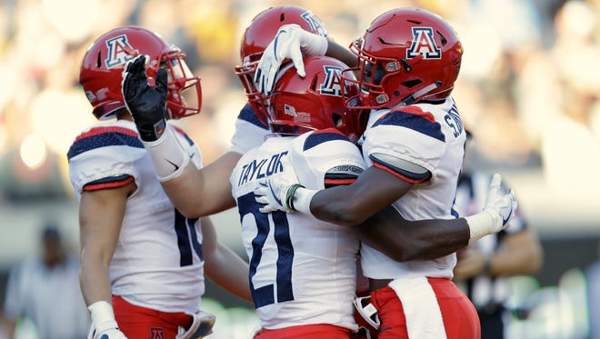 Arizona running back J.J. Taylor (21) is hugged by teammates after scoring on a rushing touchdown against California during the first half of an NCAA college football game Saturday, Oct. 21, 2017, in Berkeley, Calif. (AP Photo/Marcio Jose Sanchez)