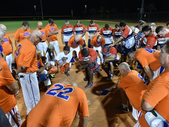 Teams huddle in grateful prayer during the battle between The Louisville Slugger Warriors and Team Florida at North Collier Regional Park.