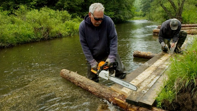 Frank Weeks works with a river bank restoration crew helping to curb erosion along the Genesee River in Gold, Pa.