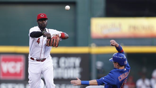 Cincinnati Reds second baseman Brandon Phillips (4) turns the double play on the Chicago Cubs left fielder Chris Coghlan (8) and second baseman Javier Baez (9) in the first inning at Great American Ball Park.