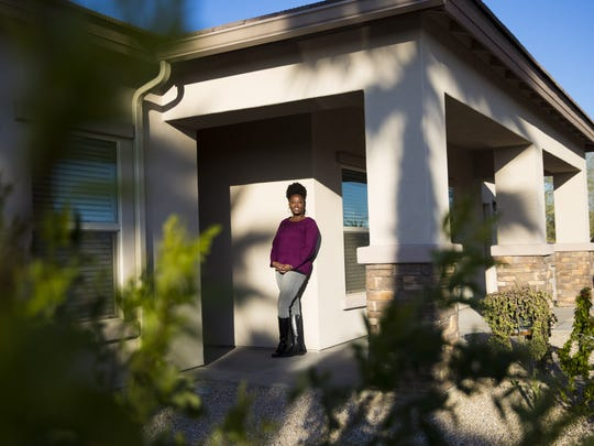 Sha Wanda Brewer stands outside her new house in Phoenix, Ariz. on February 25, 2018. With mortgage applications low for African Americans and rejection rates high, the 39-year-old received help from a housing nonprofit to buy her first home.