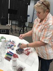 Connie Nehring gets things ready for a Christmas ornament making class she will conduct at Crimson Charities, West Allis