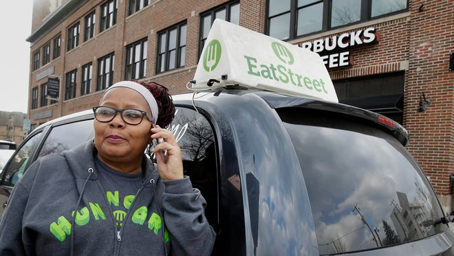 Tonya Moore, a driver for EatStreet, takes a delivery order at Starbucks on Milwaukee's east side. More than 440 restaurantsare using EatStreet for their Order Now feature on Instagram.