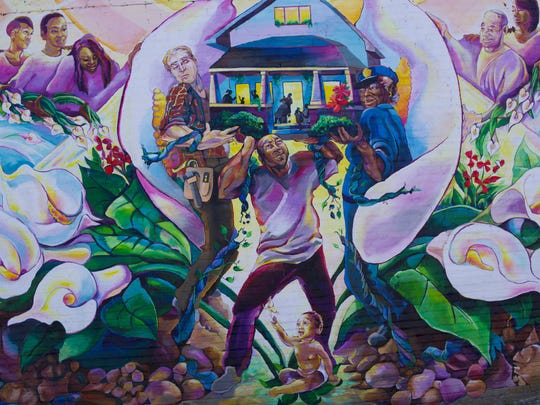 At the center of the mural stands a man holding up a home, supported by a police officer and a builder.