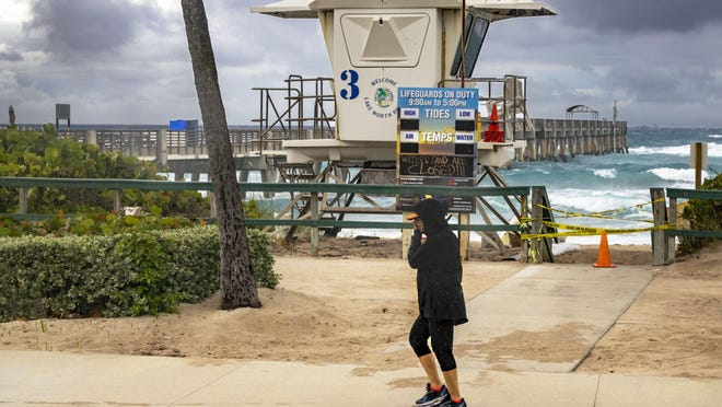 A woman walks along the sidewalk at the beach as it rains Friday in Lake Worth Beach.