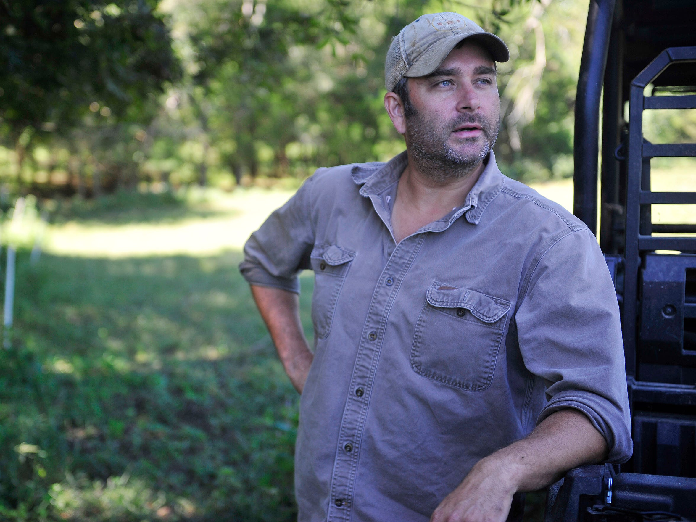 Adam Deal takes a break before he feeds his Burkshire pigs on his 300-acre farm in Shelbyville, Tenn.