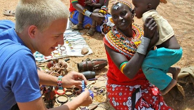Michael Best buys bead work from Mary of the Sambura village during his last trip to Africa in 2011. Best was a junior at St. Henry District High School. The 20-year-old returns in September 2015 to help the villagers he befriended in 2007.