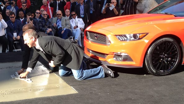 Joe Hinrichs, Ford's president of the Americas, and behind him, Raj Nair, a group vice president, brand Mustang's name into wet cement at the TCL Chinese  Theatre in Hollywood