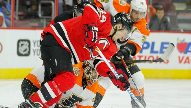 New Jersey Devils' Miles Wood, front, digs for the puck over Michal Neuvirth.