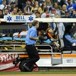Milwaukee Brewers third baseman Elian Herrera is carted off the field after a collision with left fielder Shane Peterson (not pictured) while chasing a popup in the eighth inning during the game against the Cincinnati Reds at Miller Park.