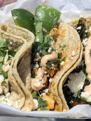A trio of tacos--including tofu and kimchi--are a popular