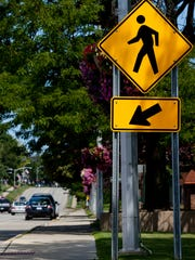 A crosswalk sign is displayed on Riverside Avenue (M-29) in St. Clair.