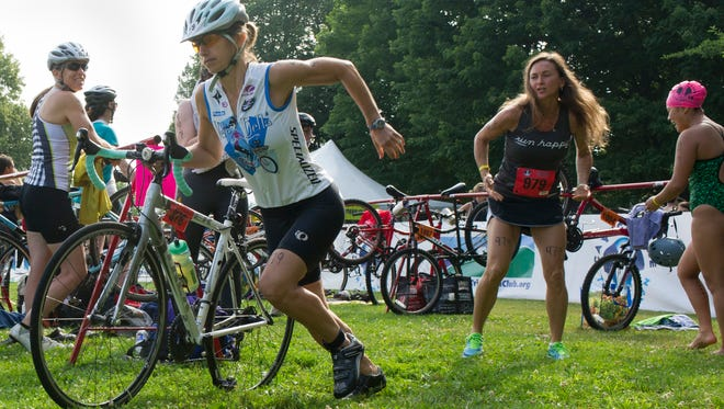 Lynn Trudell of the Tri-Babies races through the bike paddock after teammates Teressa Sawester and Jill Lidsky helped with the transition from swimming to biking. The Tri-Babies came in 1st place in the women's relay at Sunday's Cayuga Lake Triathalon.