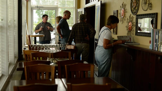 At left, Eric Fowle greets people during the Wisconsin Ledge AVA Celebration at Ledgestone Vineyards on Saturday in Greenleaf.