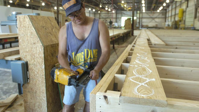 Antonio Barcenas a floor builder at Pittsville Homes nails together a section for the home in the shop. After 40 years in business, Pittsville Homes closed June 30.