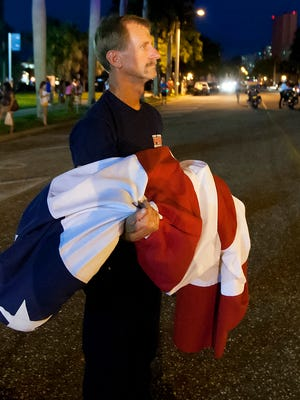 Fort Myers firefighter Keith Cortner prepares to hoist the American Flag in honor of fallen officers Saturday.