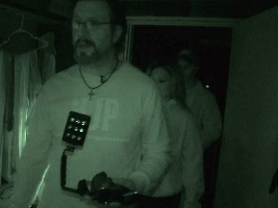 Members of New Jersey Paranormal, John Ruggiero, Krista Therrien in the middle, and John DeMattico in the back,  investigating a building.