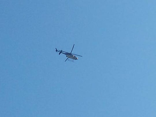 A state police helicopter circles over the York Township area Friday.