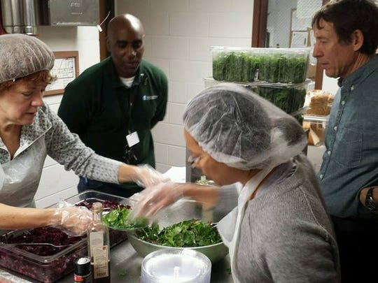 Tom Main (right) of Tinker Street Restaurant works with other volunteers to prepare a meal for Wheeler Mission residents.