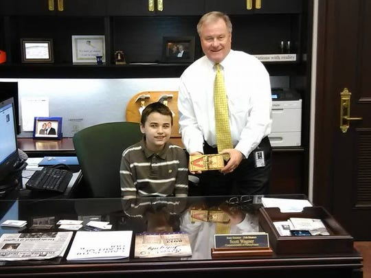 Zach Foller, a Dover Elementary School sixth grader who was recently diagnosed with autism, poses with Sen. Scott Wagner behind his desk. Foller was invited to the Capitol after a story circulated that no one came to his birthday party.