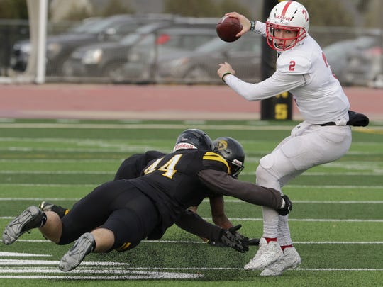 St. John's quarterback Jackson Erdmann is pressured as he tries to throw the ball during his team's loss to Wisconsin-Oshkosh in the second round of the NCAA Division III playoffs. Erdmann will be back after spending time as the team's starting quarterback last season.