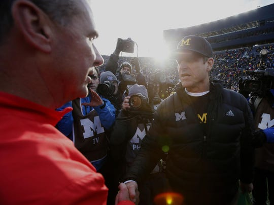 Ohio State coach Urban Meyer shakes hands with Michigan coach Jim Harbaugh, right, on Saturday in Ann Arbor. The Buckeyes beat Michigan 42-13.