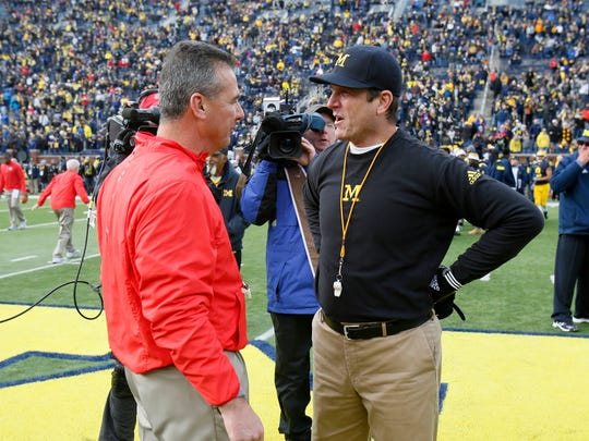 Ohio State head coach Urban Meyer and Michigan head coach Jim Harbaugh stand at midfield talking as their teams warmed up for their football game on Saturday, November 28, 2015, in Ann Arbor.