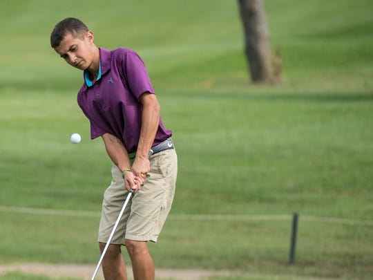 Josh Grafft watches his chip shot during the first day of play at the Calhoun County Amateur Golf Tournament at Binder Park Gold Course on Saturday.