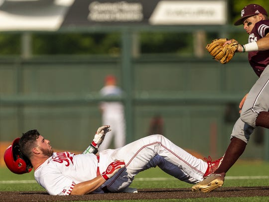 Texas A&M's Michael Helman gets the tag out and collides