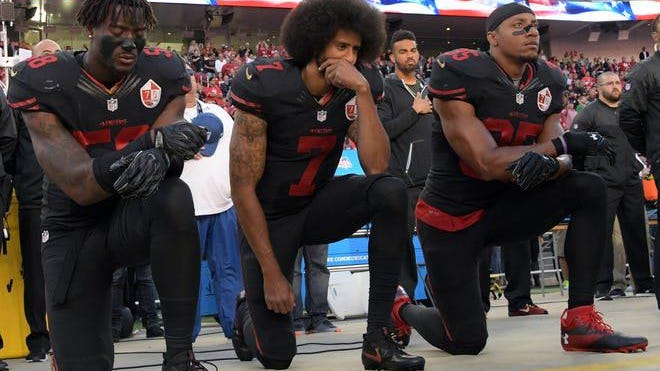 Colin Kaepernick, and 49ers teammates Eli Harold and Eric Reid, kneel in protest during the playing of the national anthem on Oct. 6, 2016.