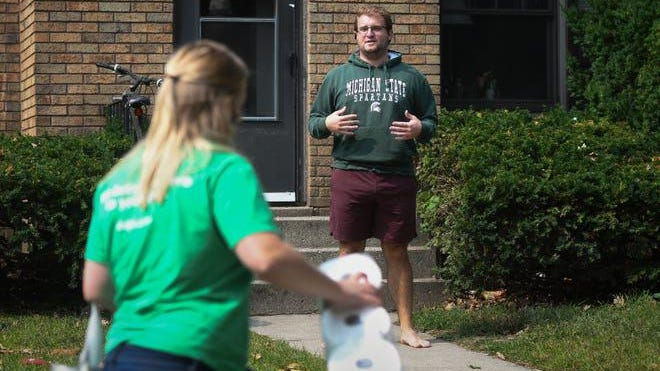 """""""You can just drop them on the sidewalk,"""" MSU senior Noah Terech says to Shipt delivery driver Anna Lindoff, Tuesday afternoon, Sept. 15, 2020. Terech tested positive for COVID-19 last week and is quarantining in the house he shares with three other students on Grove Street in East Lansing."""