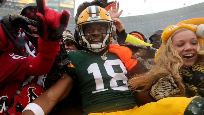 Green Bay Packers wide receiver Randall Cobb does a Lambeau Leap after his touchdown catch during a victory over the Houston Texans at Lambeau Field.