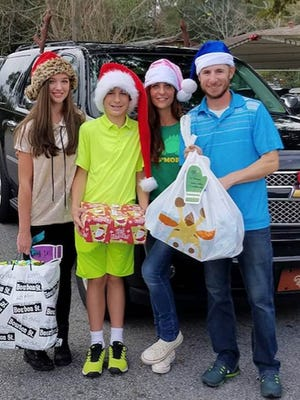 RSTC pro Josh Koivu (blue Santa hat) is ready to deliver gifts with the Francis family (far left: daughter Sarah, son Alex and mom Christy) to Lincoln Park Primary School and O.J. Semmes Elementary recently.